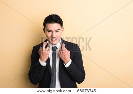 young Asian business man give you a gesture of fake, closeup portrait on studio yellow background