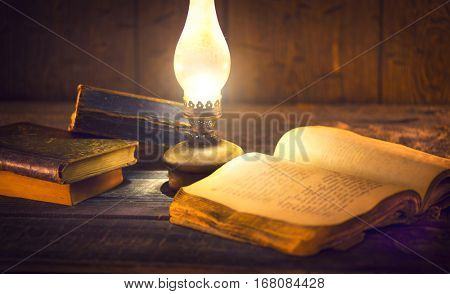Old oil lamp and old books in darkness. Vintage kerosene lantern and open old book with blank pages on wooden table.