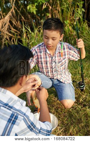 Man taking fish off the hook for his son