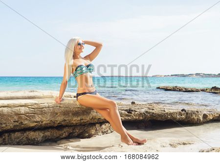 Beautiful woman in bikini. Young and sporty girl posing on a beach at summer.