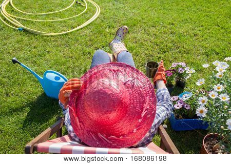 Woman gardener wearing wellington boots and straw hat have a coffee break while working in the garden.