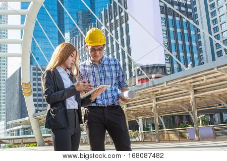 Architect and Assitant or Secretary discussing while holding Wireless Digital Tablet in Modern City Building Construction site as Business Industry Technology Concept.