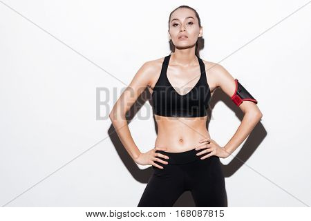 Confident young fitness woman with armband in black sportswear over white background poster