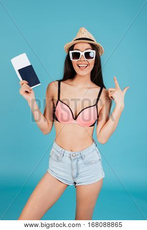Picture of happy young lady with long hair wearing hat and dressed in swimwear posing over blue background holding passport