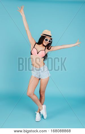 Photo of happy young woman with long hair wearing hat and dressed in swimwear posing over blue background