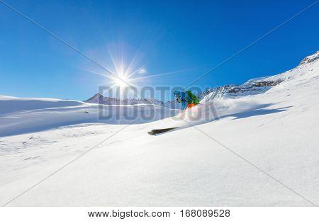 Freerider skier running downhill in beautiful Alpine landscape. Fresh powder snow, blue sky on background.