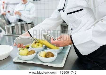 Chef preparing plates in gastronomic canteen facility