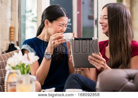 Two young women laughing while using a tablet indoors at a coffee shop