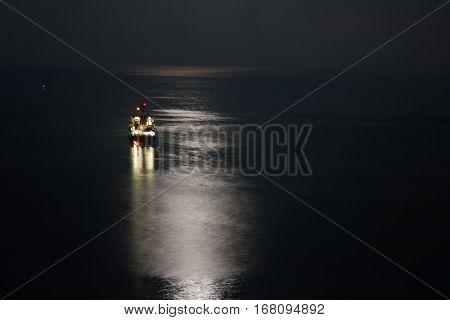 Seascape with lunar path on black sea.