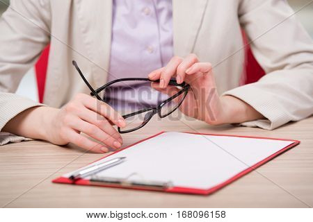 Hand holding glasses at the working desk