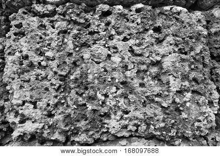 background and abstract porous texture of an old stone surface of monochrome tone