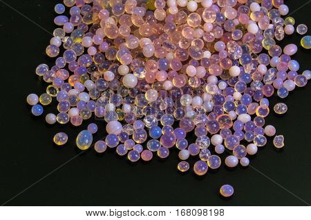 Macro of silica gel balls laying on black background.Its use to prevent mold, mildew, corrosion, odours and other moisture damage.