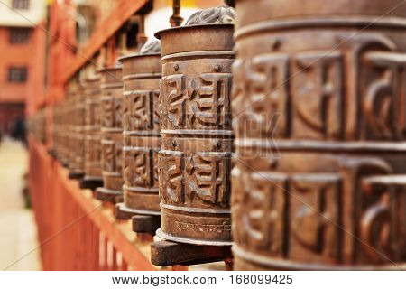 Line of copper praying drums in buddhist monastery
