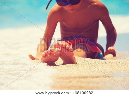 feet of little boy relax at summer sand beach