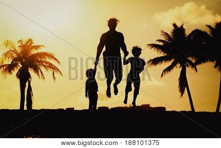 father with little son and daughter jumping at sunset tropical beach