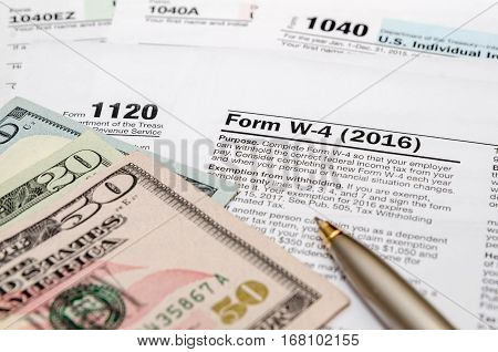 tax form w4 1040 1120 with pen and us dollar