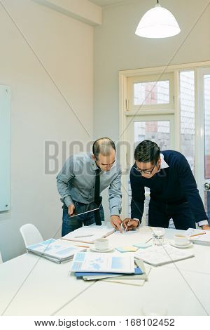 Two business people examining documents at table