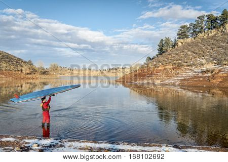 male paddler in drysuit is launching stand up paddleboard on a lake in Colorado, winter scenery