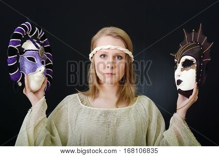 beautiful actress holds the theatrical mask on a dark background