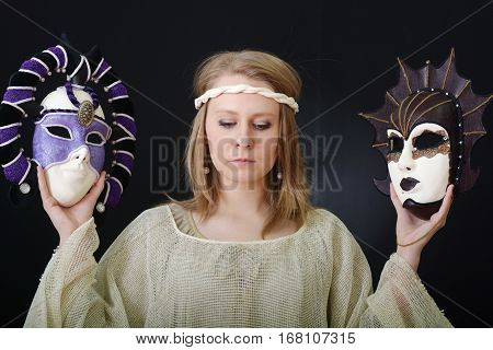 blonde girl with blue eyes in a theatrical mask on a dark background