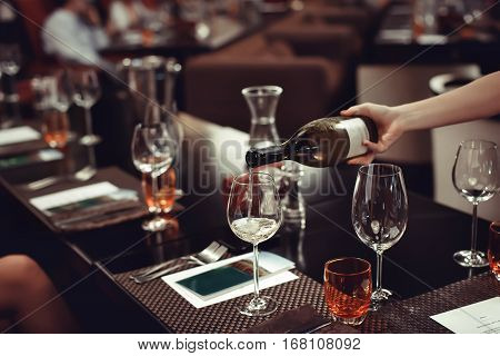 Men's hand pouring wine to the glass onthe table. There are many other glasses there