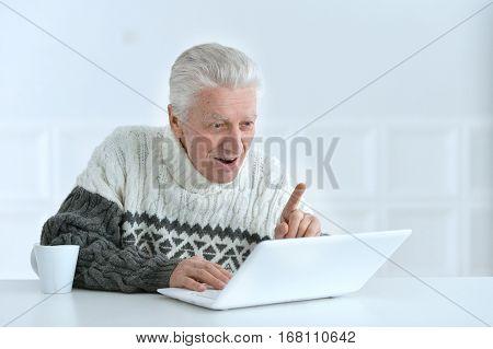 senior man working at office, using laptop