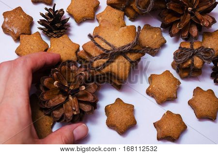 Homemade Rye Cookies Star Shaped Stack Tied With Brown Rope And Female Hand Holding One Pine Cone On