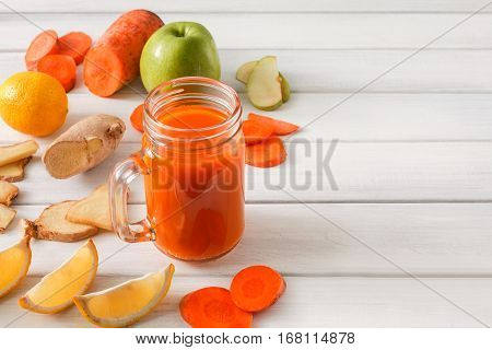 Detox cleanse drink, vegetable smoothie ingredients. Natural, organic healthy juice in glass jar for weight loss diet or fasting day. Carrot, apple, ginger and lemon mix on white wood with copy space poster
