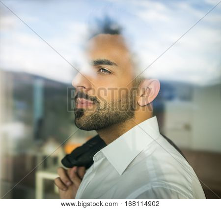 Double exposure confident attractive young man looking through the window glass
