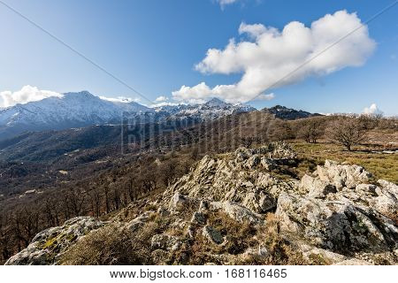 View of snow covered San Parteo viewed from Col de Battaglia in the Balagne region of Corsica with a rocky outcrop in the foreground and blue skies above