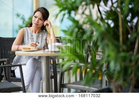 Business lady sitting in cafe and pondering over ideas