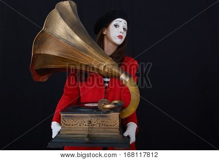 brunette girl mime holding an old gramophone on a dark background