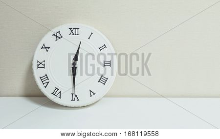 Closeup white clock for decorate show half past twelve or 12:30 p.m. on white wood desk and cream wallpaper textured background with copy space