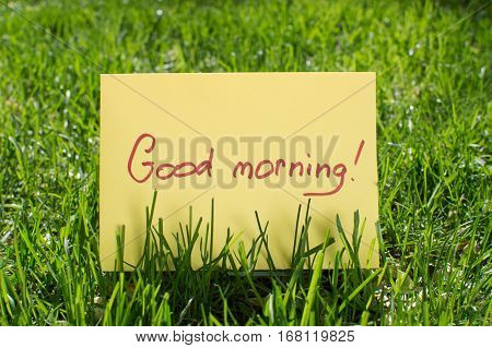 A piece of paper that says good morning lying on green grass in the park. Sunrise. A good day. Good start to the day. Cheerful morning.