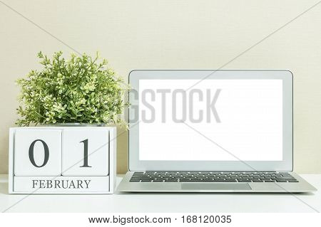 White wooden calendar with black 1 february word with white blank space at center of computer notebook on white wood desk and cream wallpaper textured background selective focus at the calendar