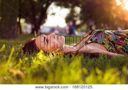 Gorgeous young beautiful girl lies on the grass in the park. Woman with beautiful make-up in a colored dress resting in a park. Dream.