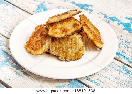 Plate with potato pancakes on the table.