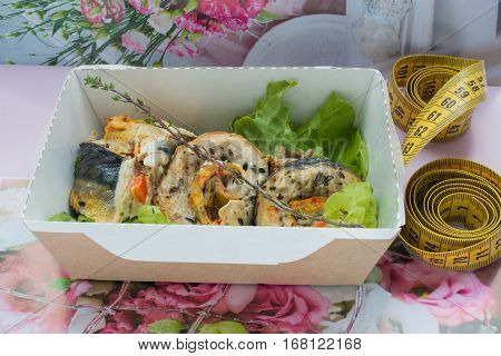 The beaters from the baked mackerel in a craft box on a on a flower background with a centimetric tape. Healthy nutrition dish.