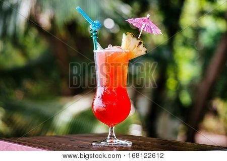 Pin Orange cocktail with ice on the background of the tropics. A cold drink in the tropics