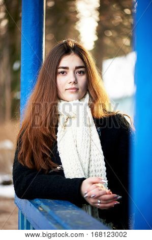 Young girl looking at the camera. Long dark hair, scarf, white chunky knit. Lifestyle
