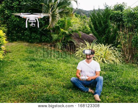 A man in a virtual reality helmet sitting next to the drone. A man sits on the grass