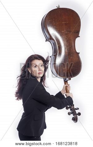 beautiful brunette woman uses cello as quirky baseball bat in studio against white background