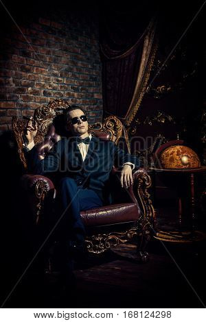 Imposing well dressed man in a classic luxurious apartments. Luxury. Men's beauty, fashion.