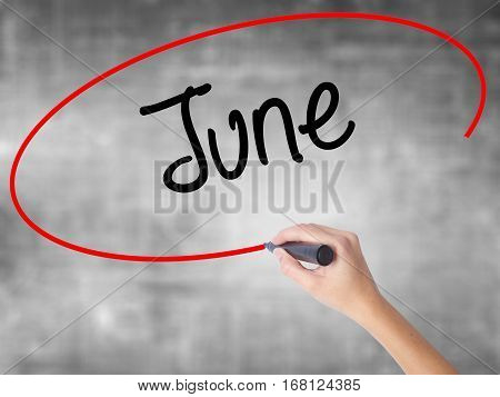 Woman Hand Writing June  With Black Marker Over Transparent Board
