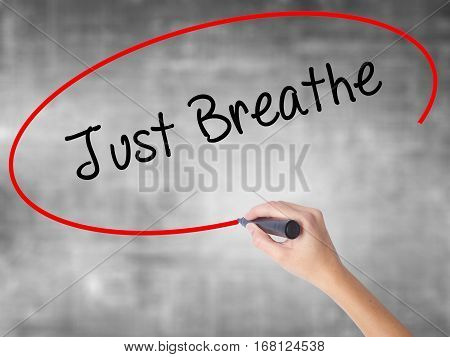 Woman Hand Writing Just Breathe With Black Marker Over Transparent Board