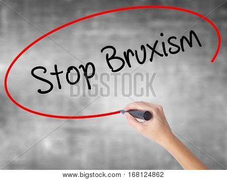 Woman Hand Writing Stop Bruxism With Black Marker Over Transparent Board