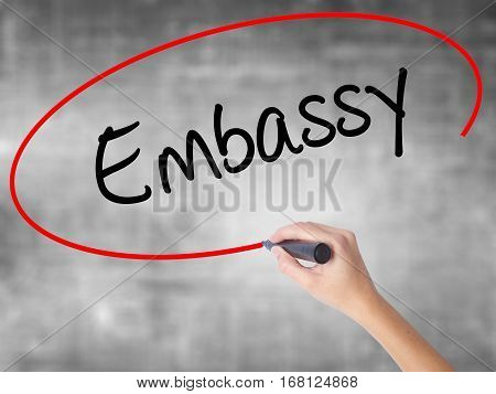 Woman Hand Writing Embassy With Black Marker Over Transparent Board