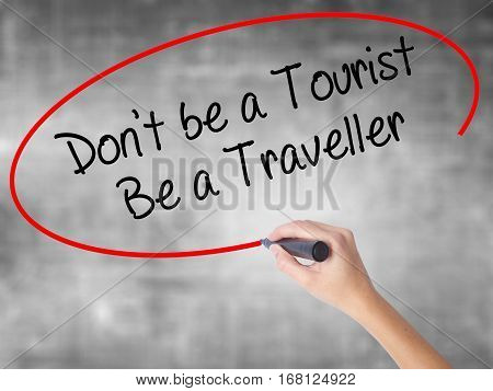 Woman Hand Writing Don't Be A Tourist Be A Traveller  With Black Marker Over Transparent Board