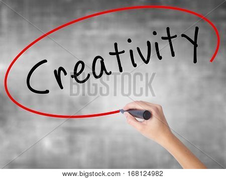 Woman Hand Writing Creativity With Black Marker Over Transparent Board