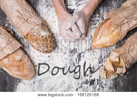 Bread dough making. Lots of different bread sorts, wrapped in craft paper. Baking and cooking concept background. Hardworking hands of baker on wooden table, sprinkled with flour.